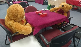 Two teddies sitting at a card table