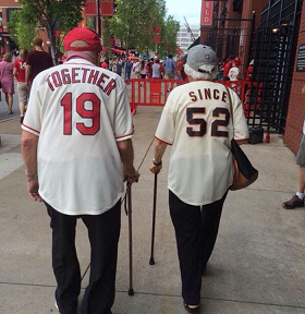 Elderly couple with shirts reading Together since 1952